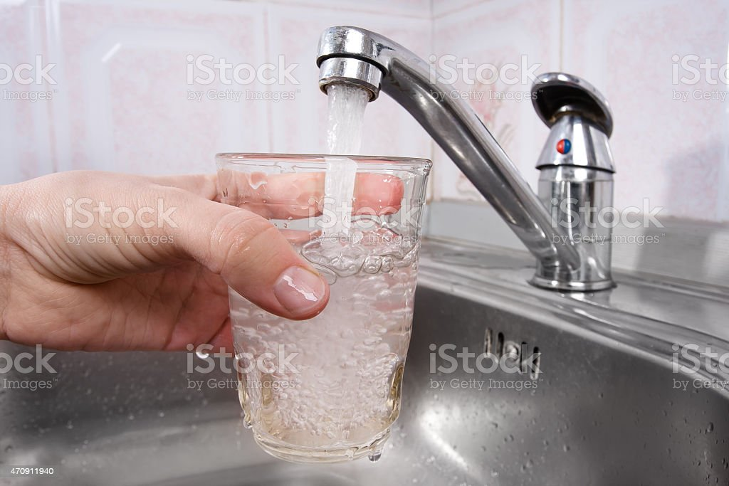 hand pours water into a glass from  faucet stock photo