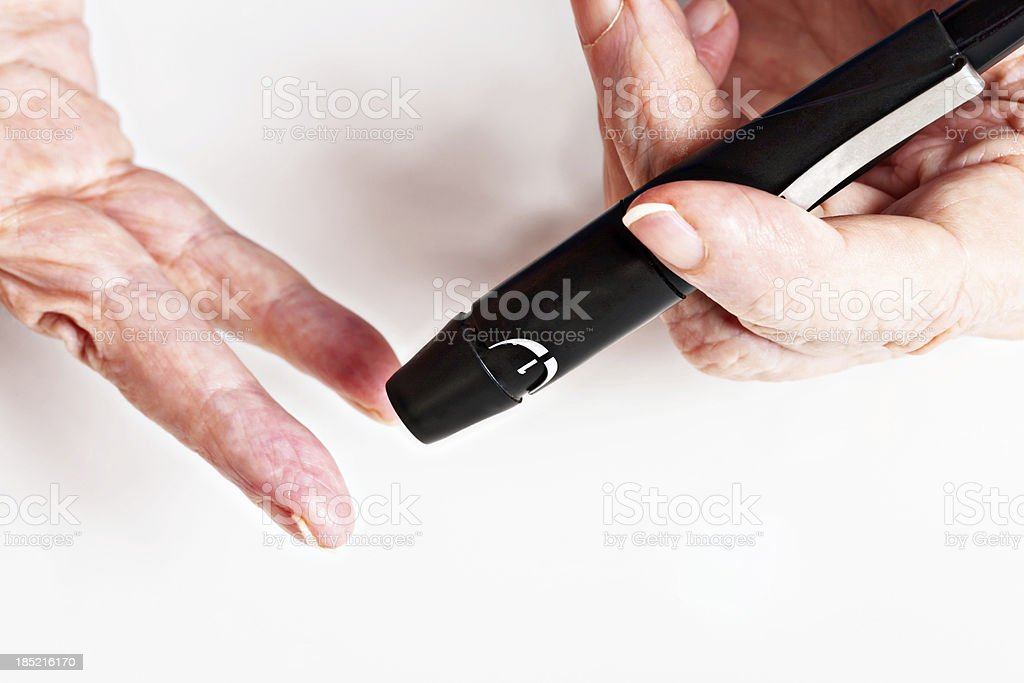 Hand prepares to use automatic lancet for drawing blood stock photo