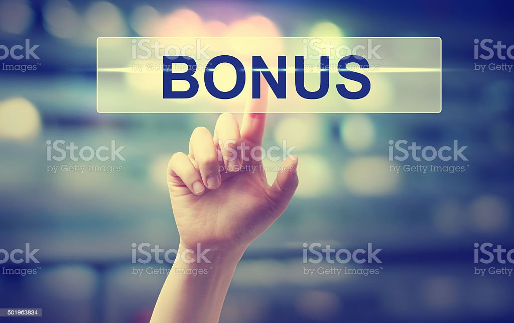 Hand pressing a bonus button on blury city lights background stock photo
