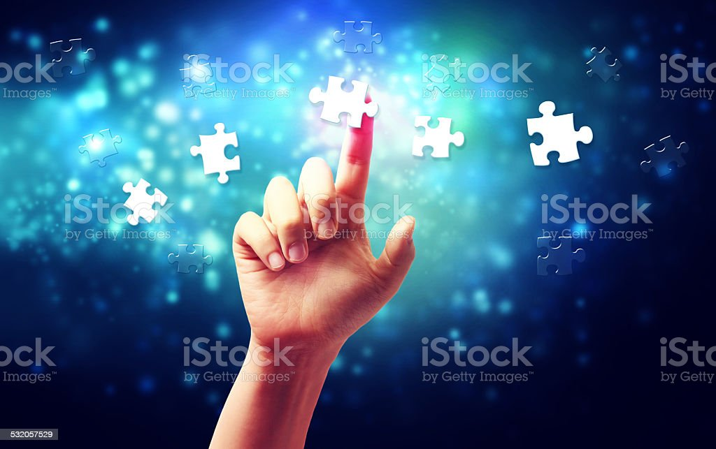 Hand pressing a piece of puzzle stock photo