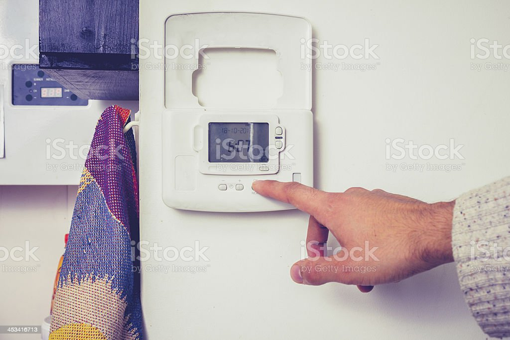 Hand pressing button on central heating controls stock photo