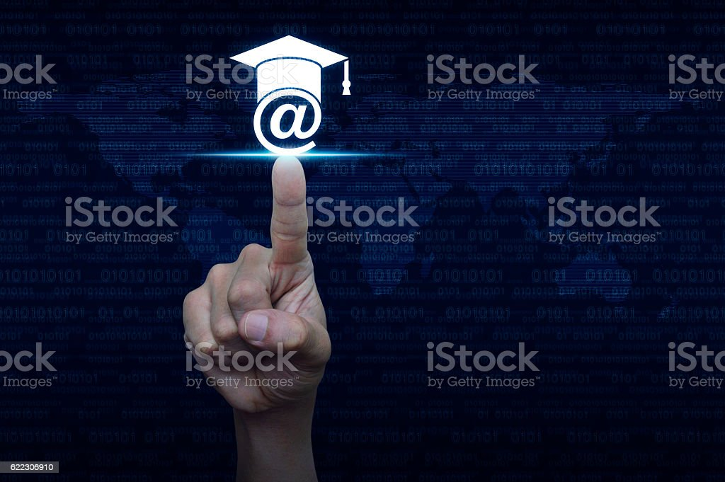 Hand pressing e-learning icon over computer binary code stock photo