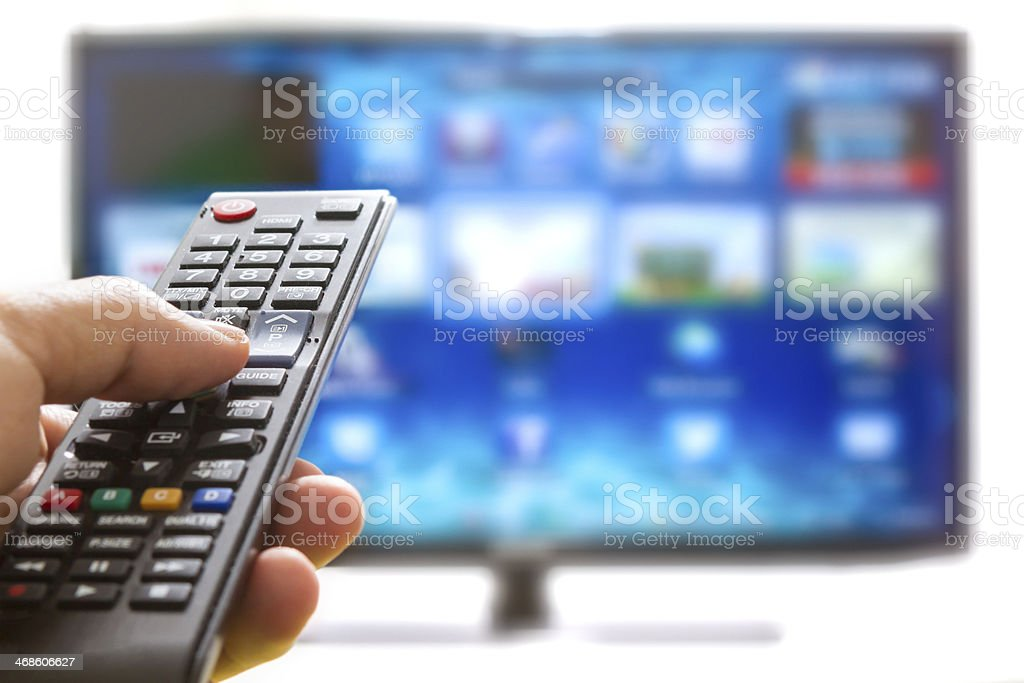 Hand pressing remote control on smart TV stock photo