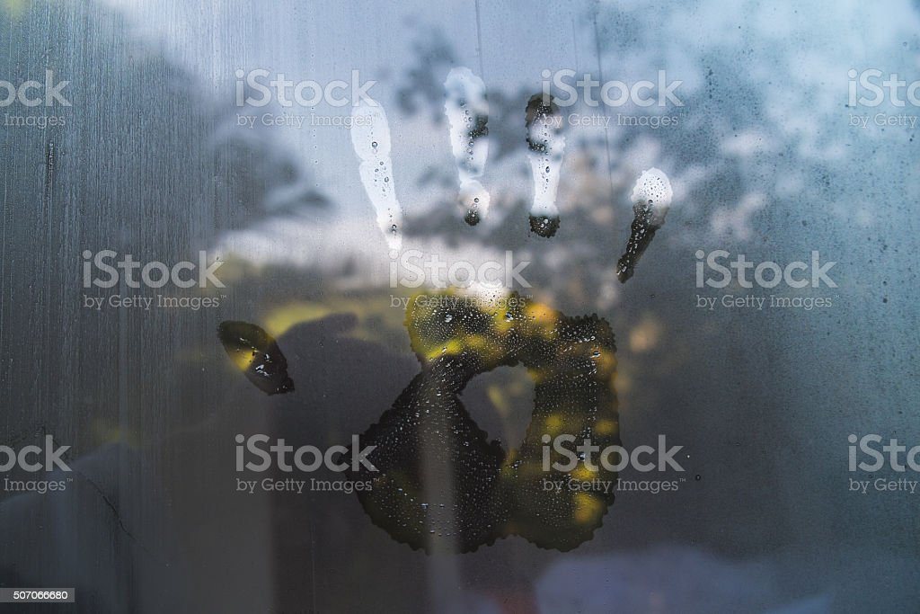 Hand print on hazy glass in the morning stock photo