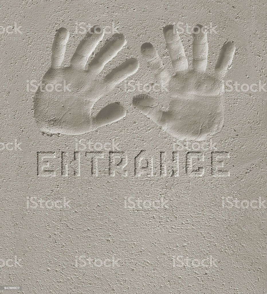 Hand prints on cement  'ENTRANCE' royalty-free stock photo