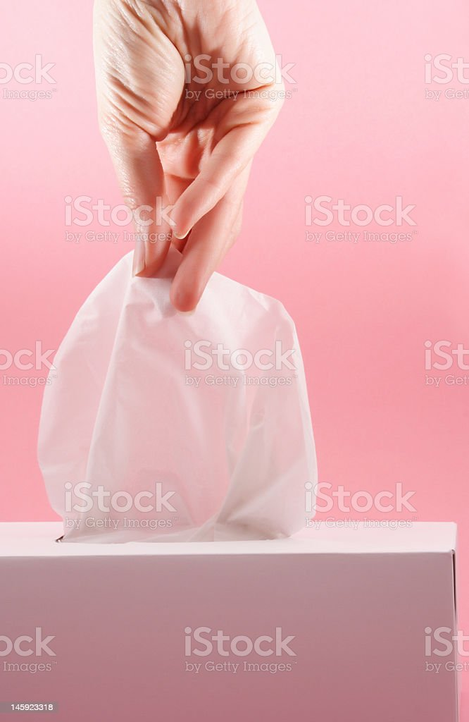 A hand pulling a tissue out of a tissue box stock photo