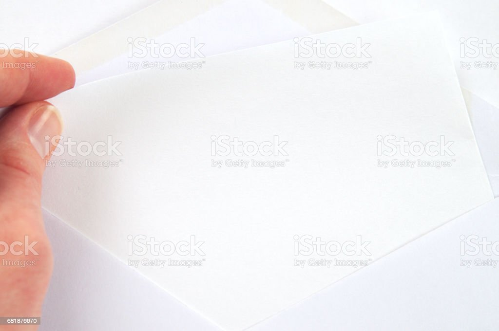 hand pulling blank sheet of paper from white envelope, white background stock photo
