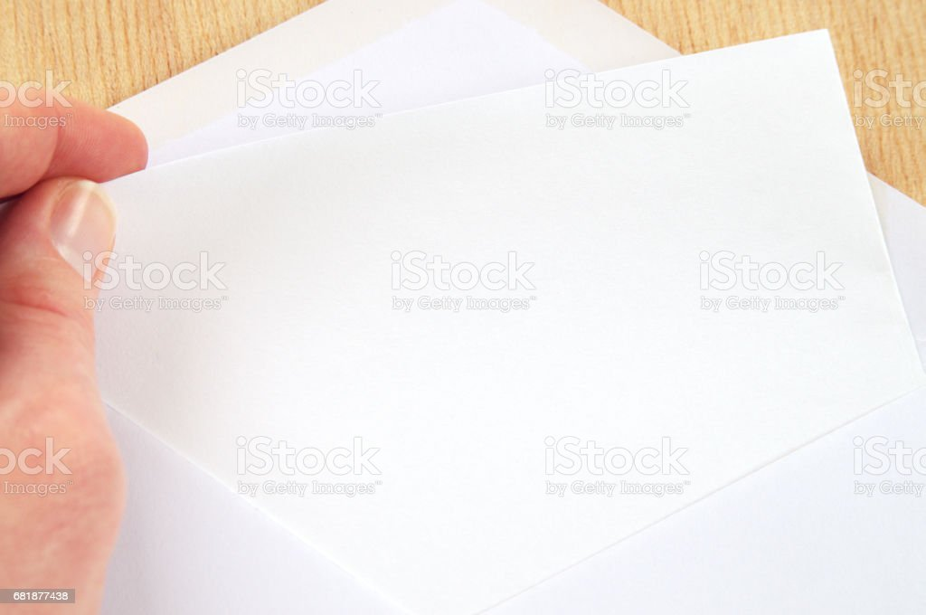hand pulling blank sheet of paper from white envelope, wooden background stock photo