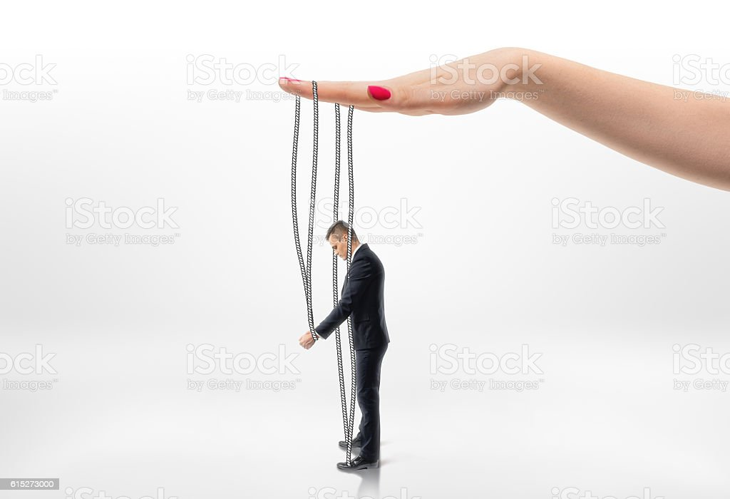 Hand pulling businessman by strings. stock photo