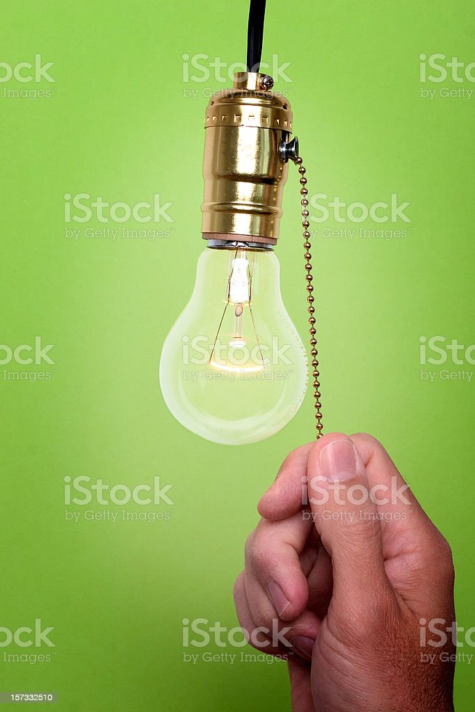 Hand pulling chain to turn off light bulb green background stock photo