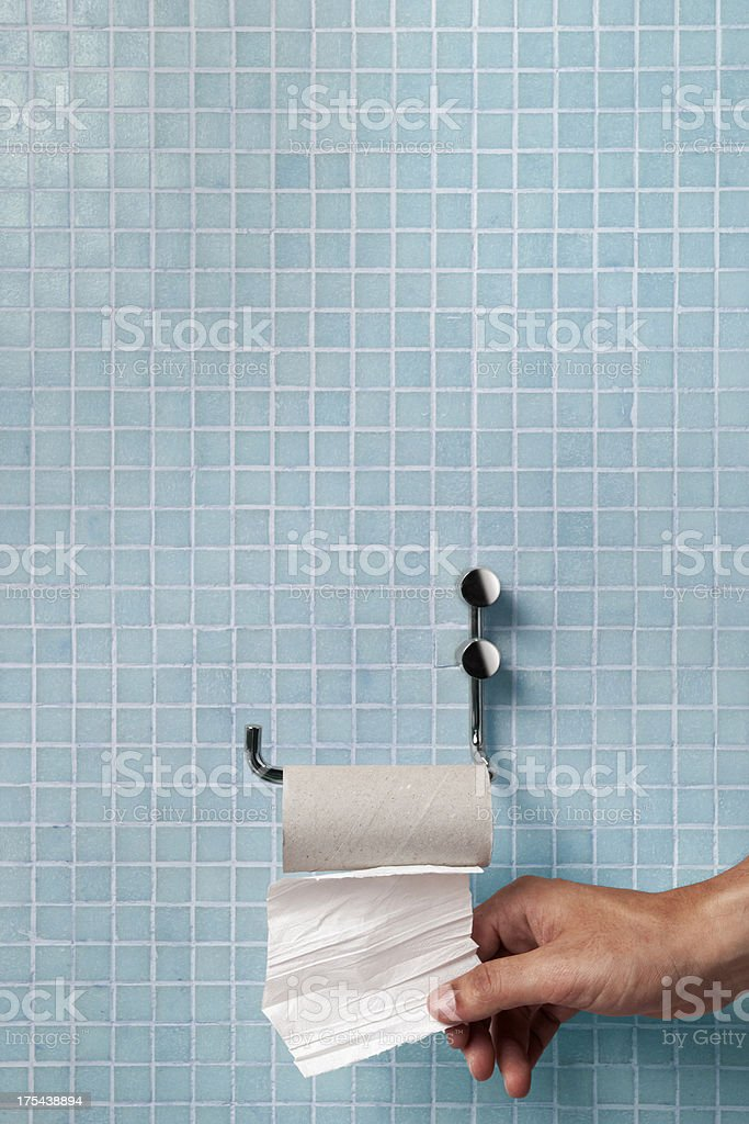 Hand pulling last square of toilet paper from the roll stock photo