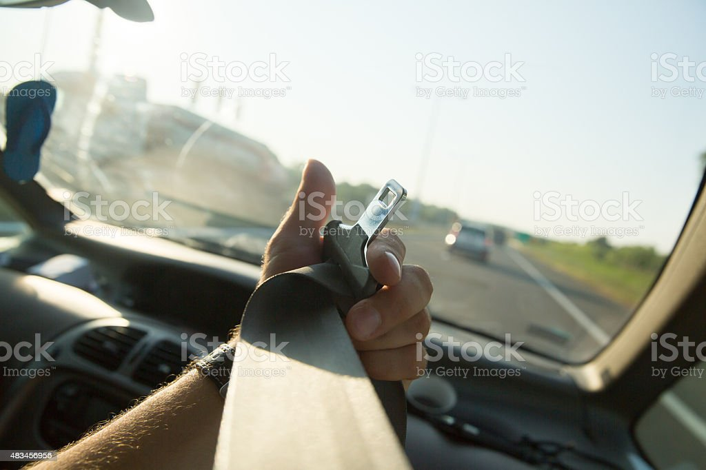Hand pulling seat belt in the car stock photo