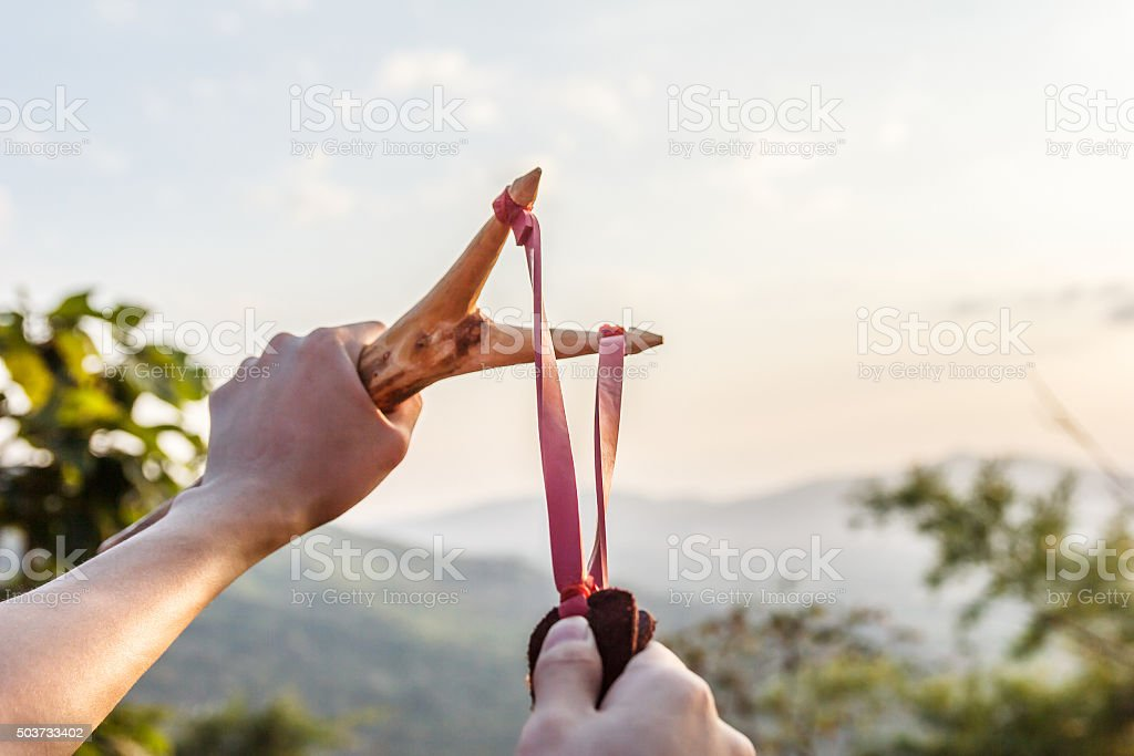 Hand pulling slingshot to shoot tree seed into forest. stock photo