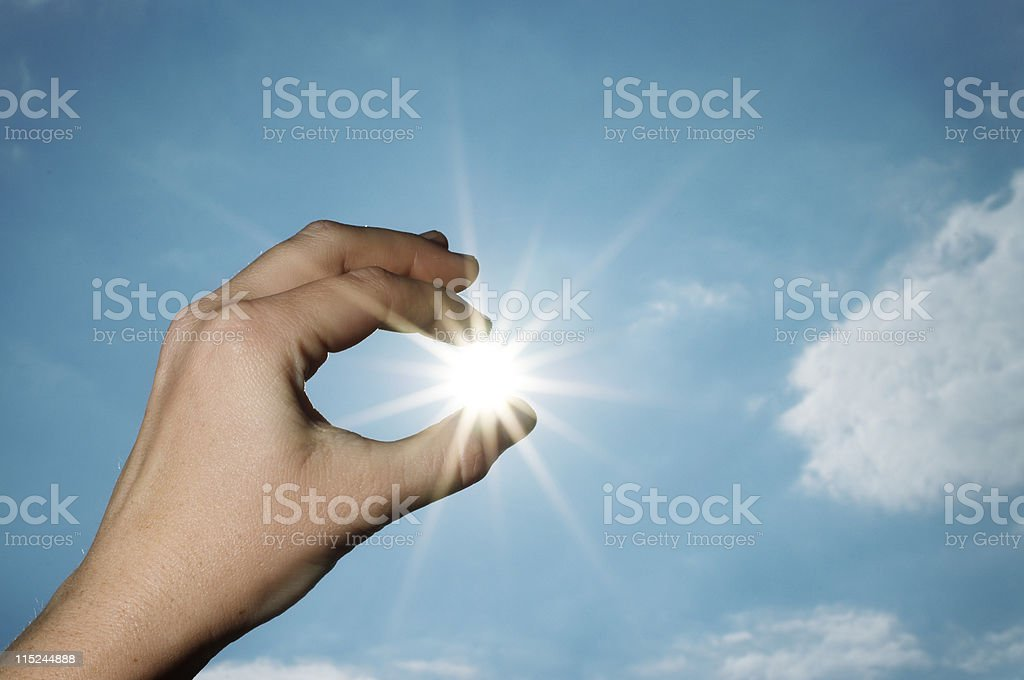 Hand pulling the sun from sky stock photo