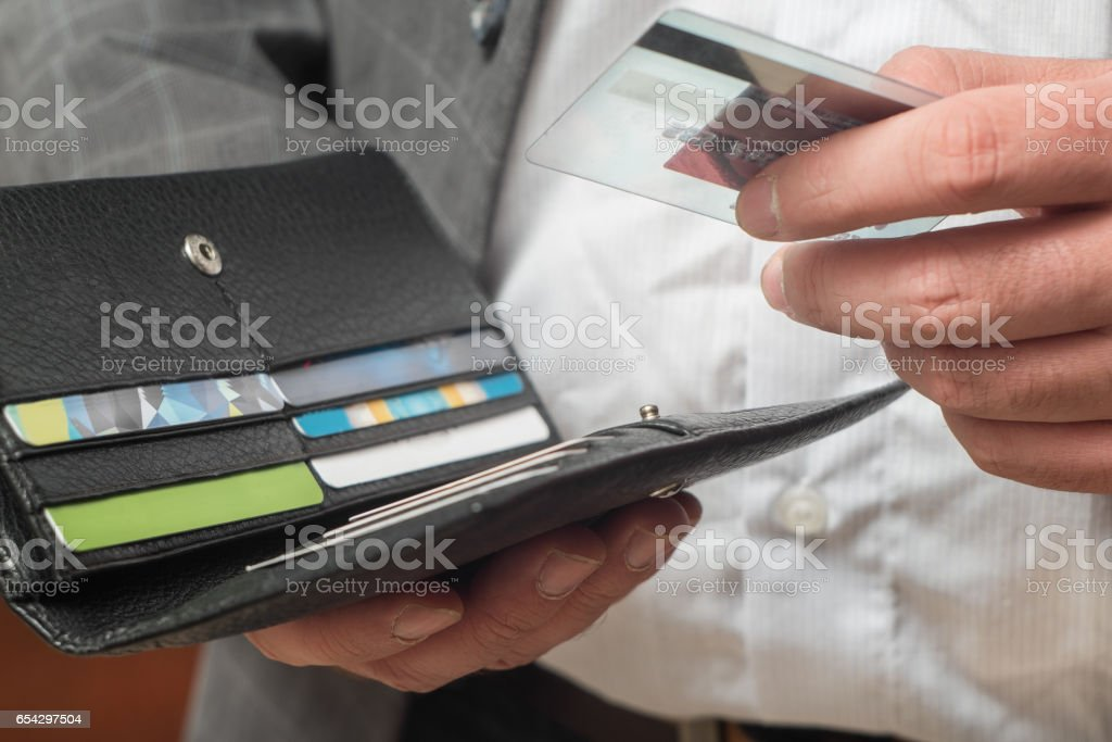hand pulls out a credit card stock photo