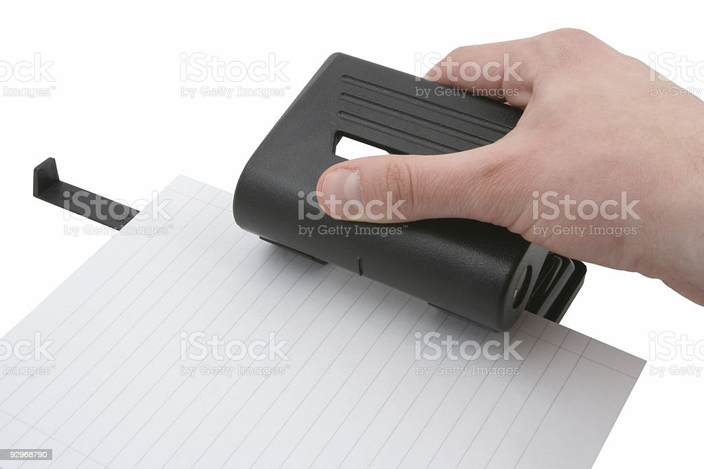 hand punching lined paper page stock photo