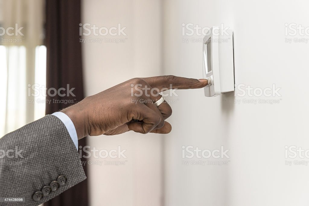 hand push button digital climate control stock photo