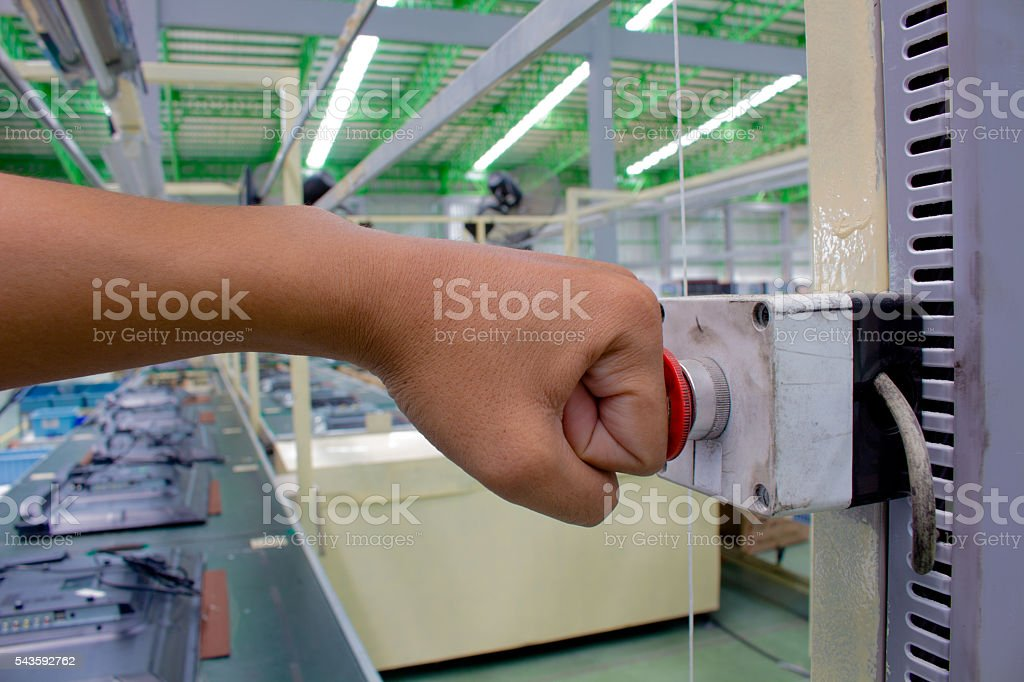 Hand push Emergency button in product line. stock photo
