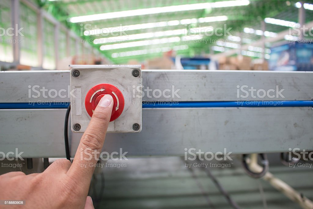 Hand push Emergency button in product line, Safety concept. stock photo