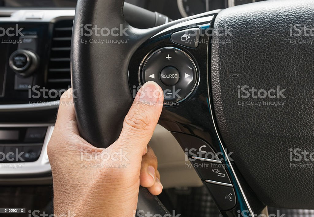 hand pushes the cruise control button on a steering stock photo