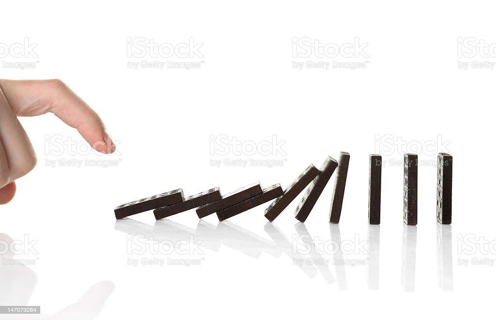 Hand pushing dominoes stock photo