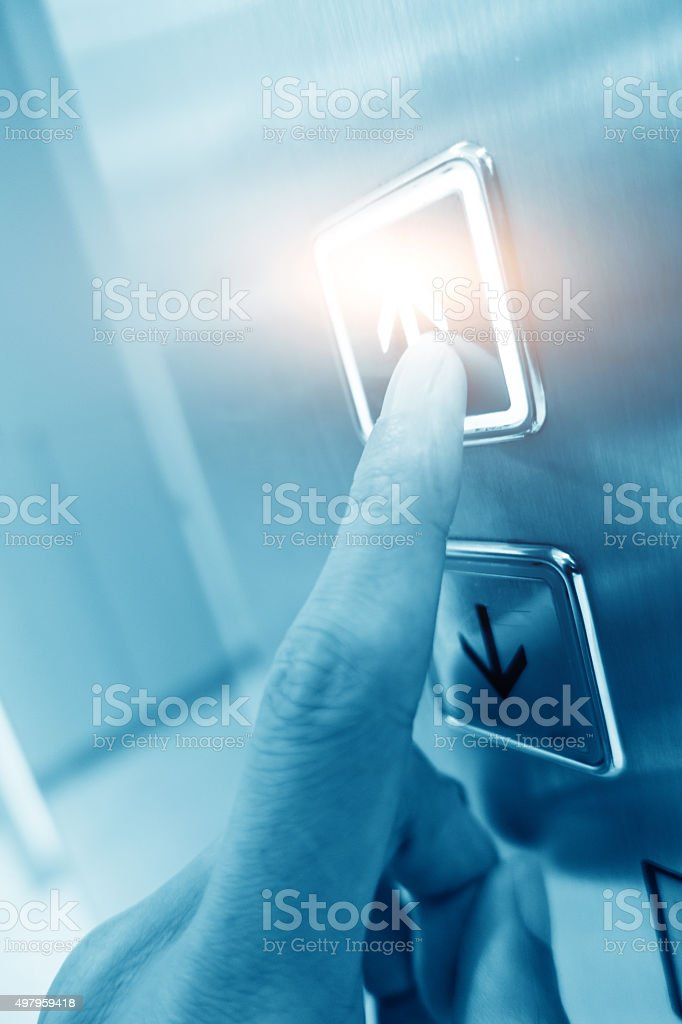 Hand pushing elevator button stock photo