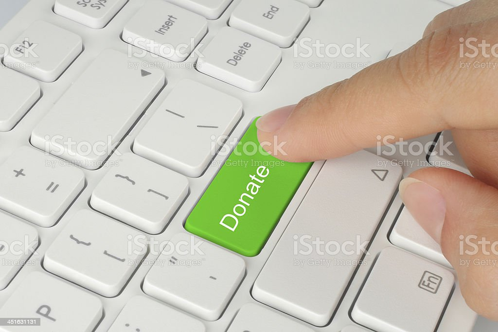 Hand pushing green donate button stock photo