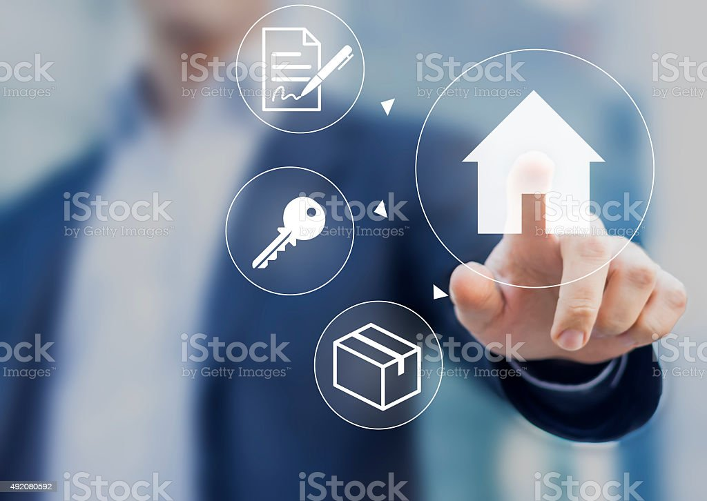 Hand pushing house button with contract, keys and boxes stock photo