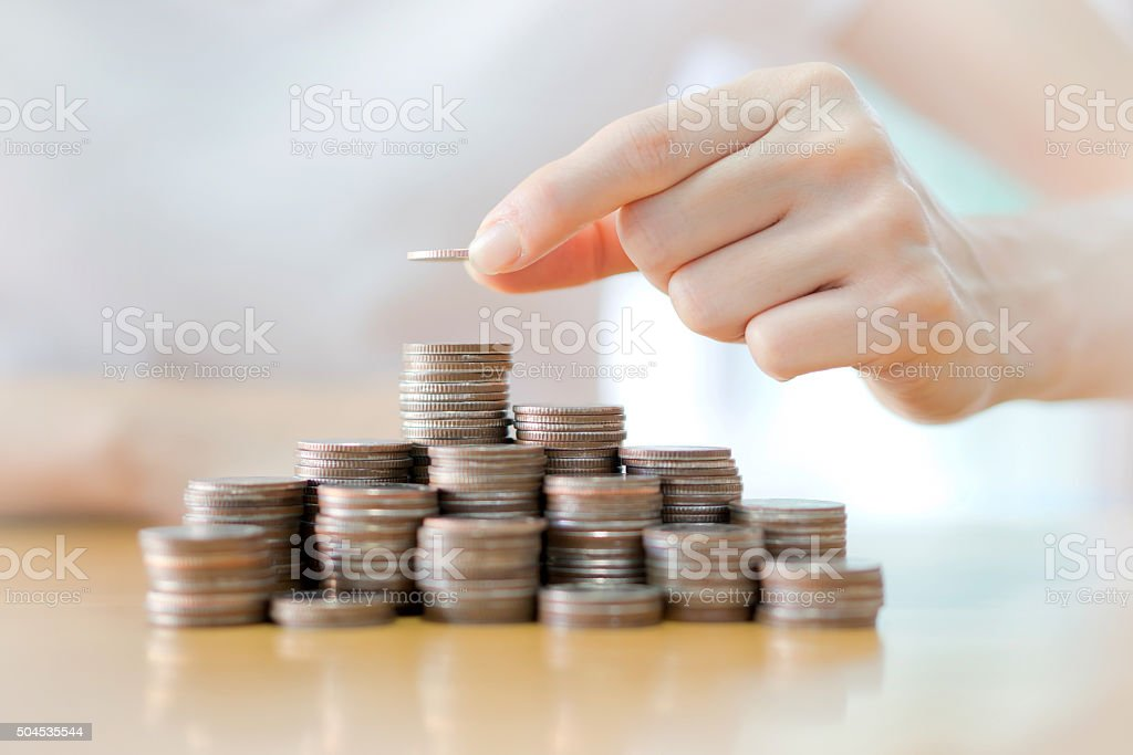 Hand put coins to stack of coins stock photo