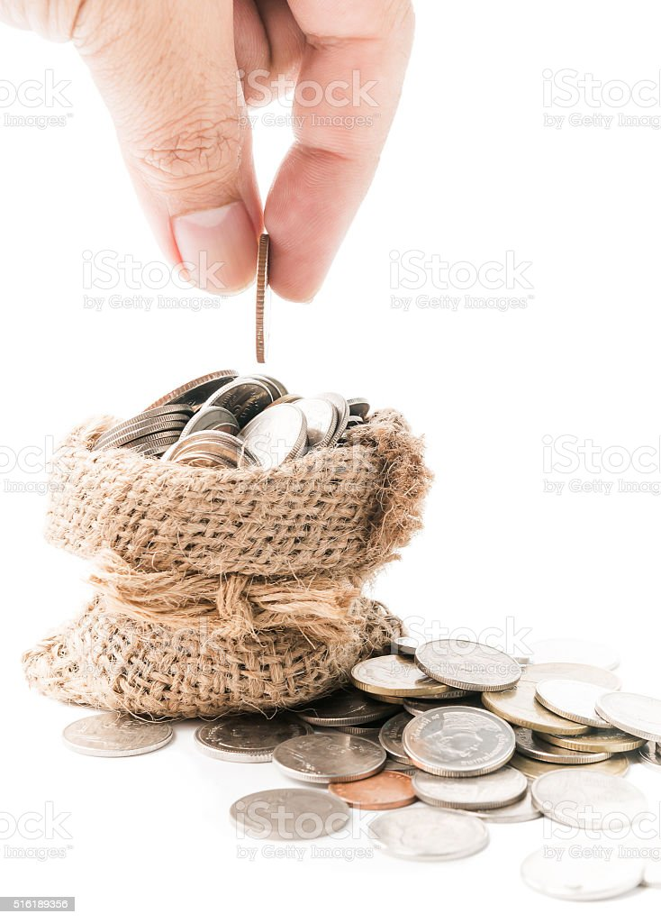 Hand put down money coin to sack isolated stock photo