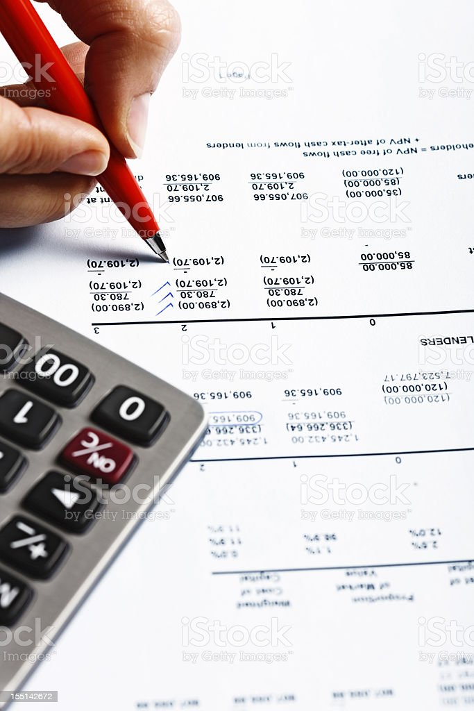 Hand puts check marks on financial spreadsheet, calculator standing by royalty-free stock photo