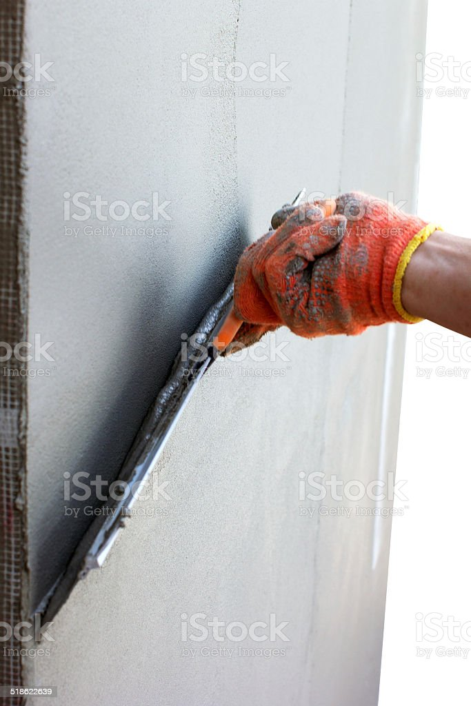hand putties a wall by putty knife for facade stock photo