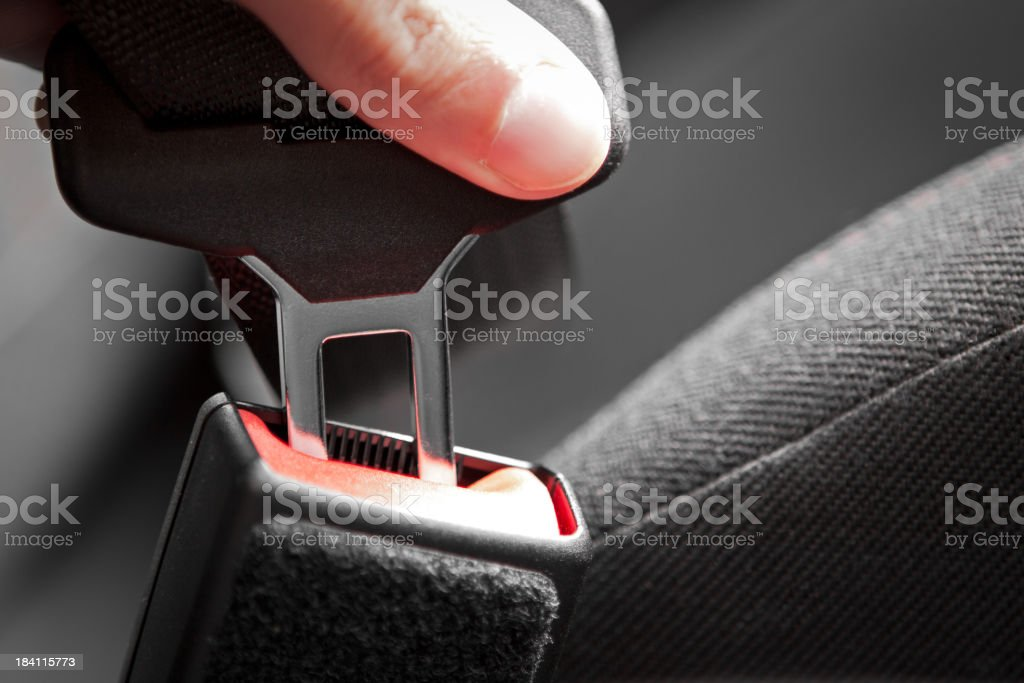 Hand putting a buckle into a car seat belt royalty-free stock photo