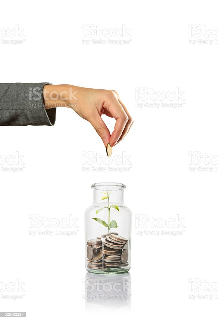 hand putting a coin in jar with plant , saving money stock photo