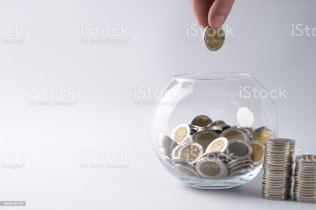 Hand putting a gold coin in glass money box stock photo