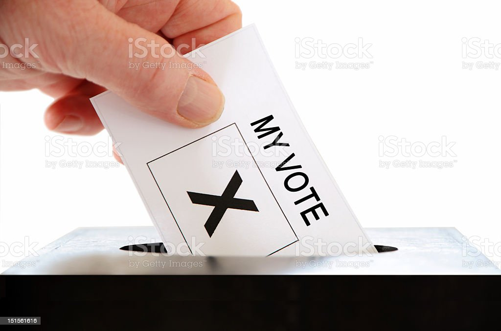 A hand putting a my vote card in a box stock photo