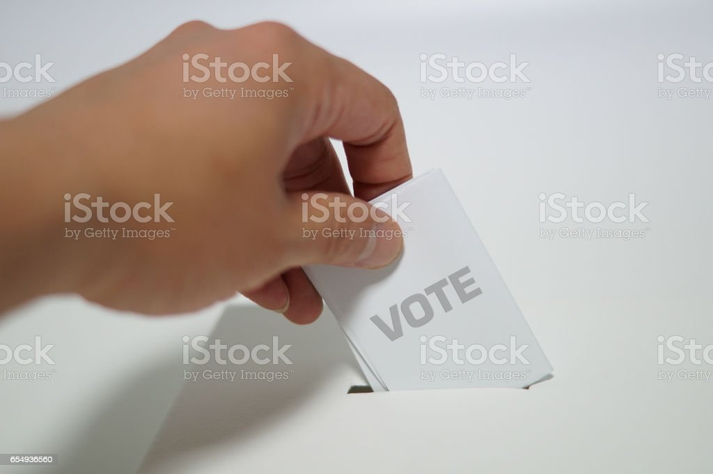 Hand putting ballot in ballot box stock photo