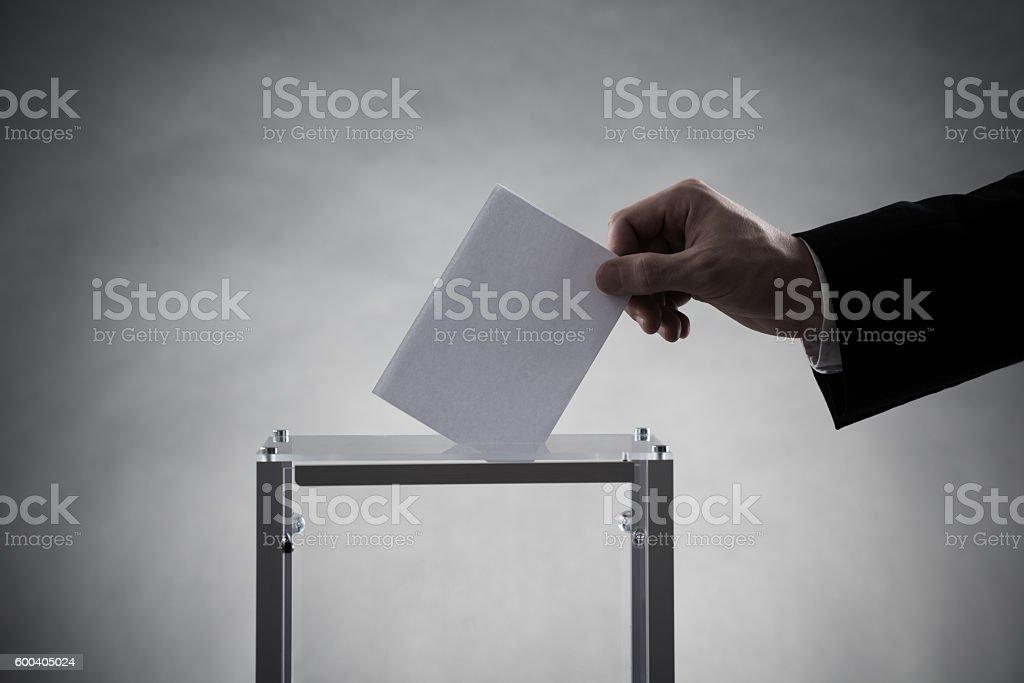 Hand Putting Ballot In Glass Box stock photo
