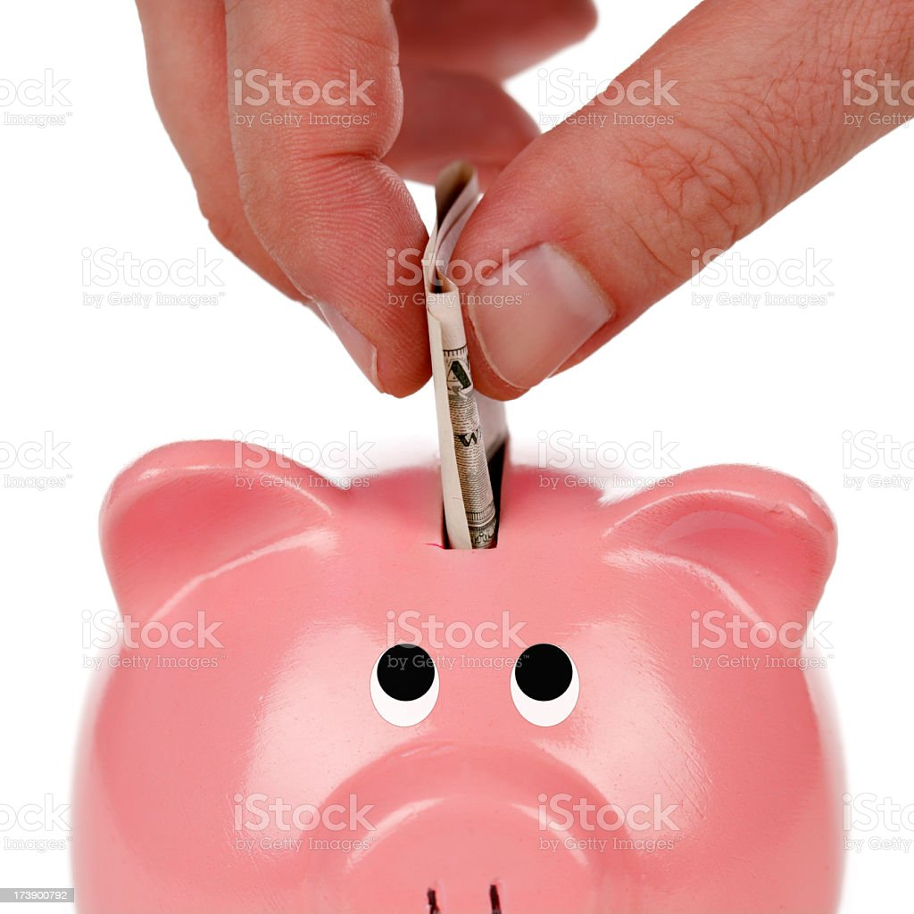 A hand putting cash into a piggy bank for savings royalty-free stock photo