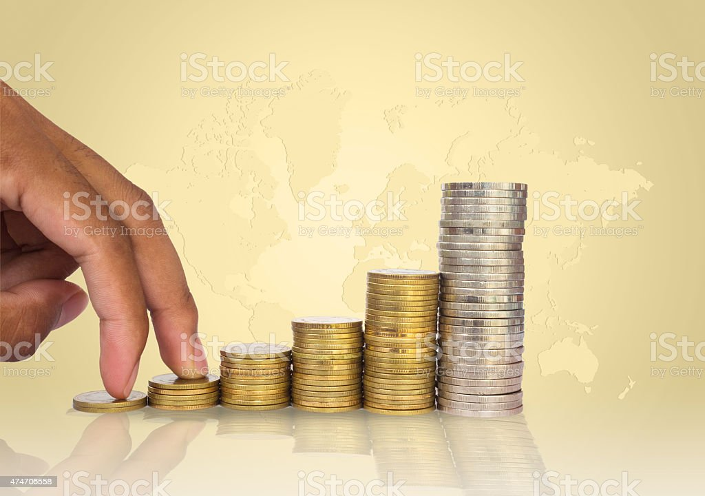 Hand putting coin stacks with world map background stock photo