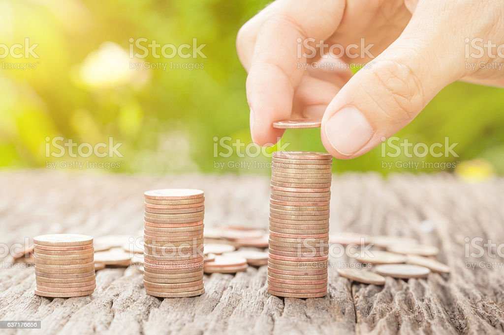 Hand putting coin to money with sunlight, business ideas stock photo