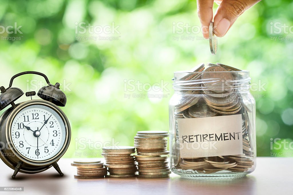 Hand putting Coins in glass jar with retro alarm clock stock photo