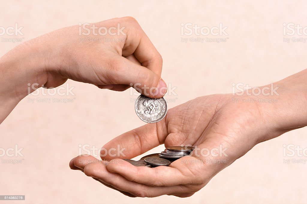 hand putting coins in the palm of another person stock photo