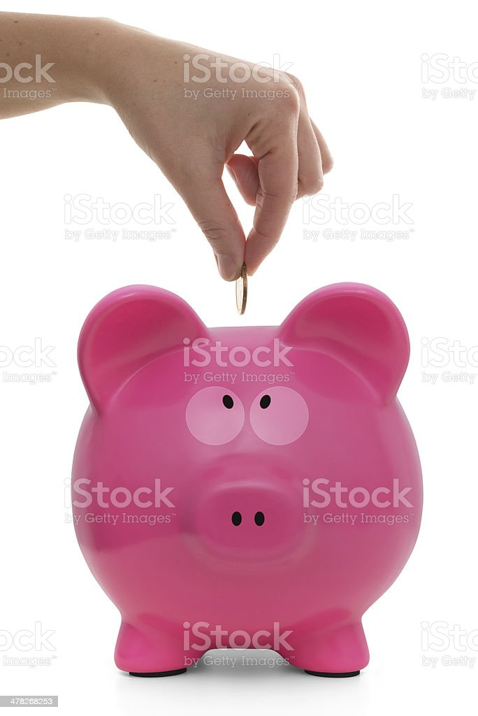 Hand putting coins into piggy bank royalty-free stock photo