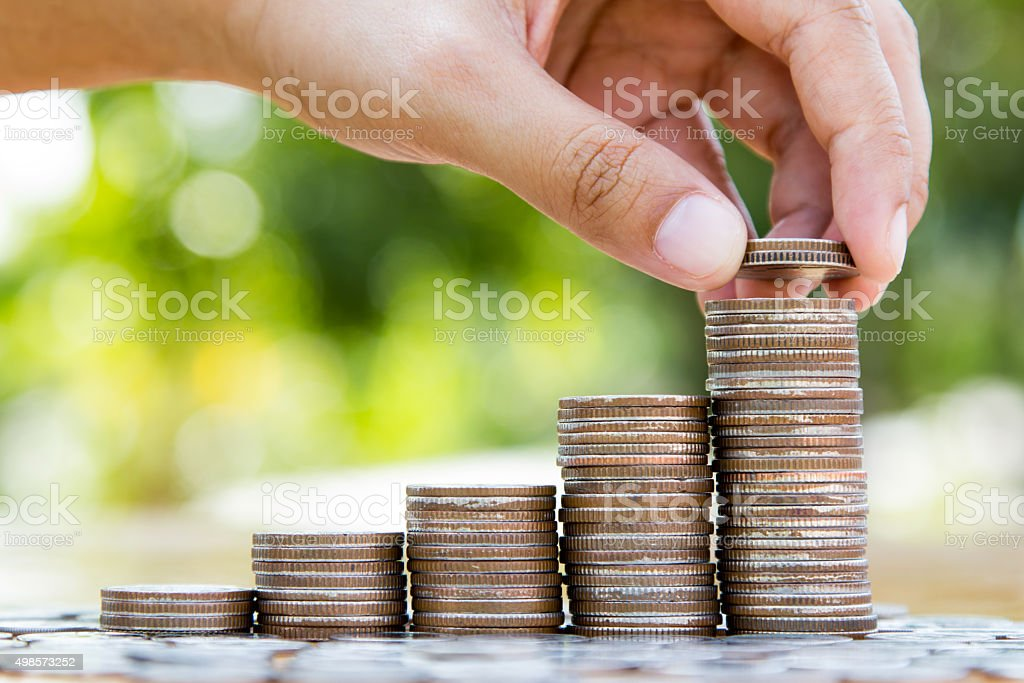 hand putting coins to coin stack growing graph stock photo
