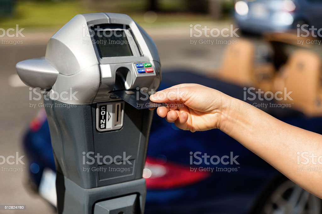 Hand putting credit card into parking meter with convertible car stock photo
