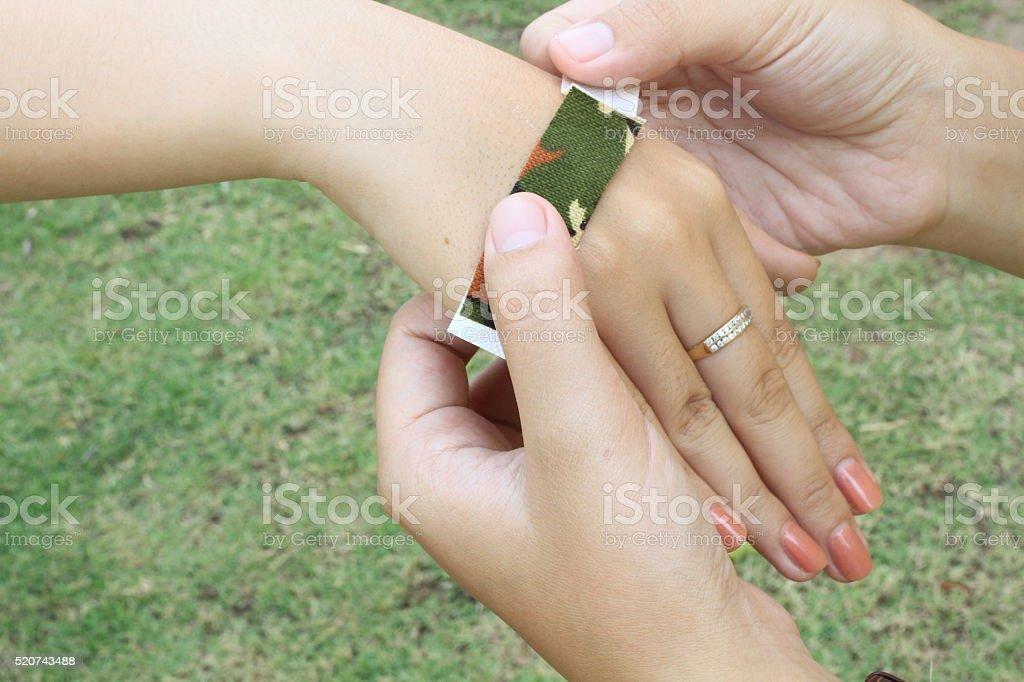 hand putting elastic plaster on hand injury stock photo