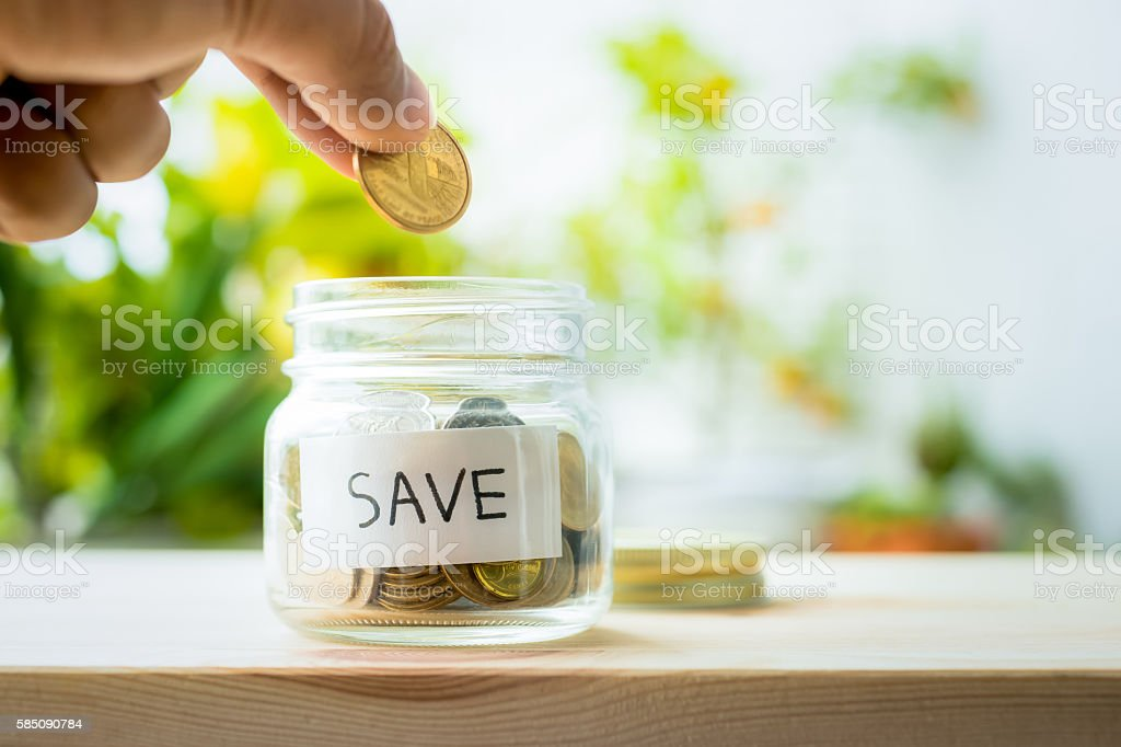 Hand putting money coin in glass jar with save word. stock photo