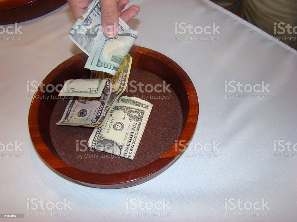 Hand putting money in collection plate stock photo