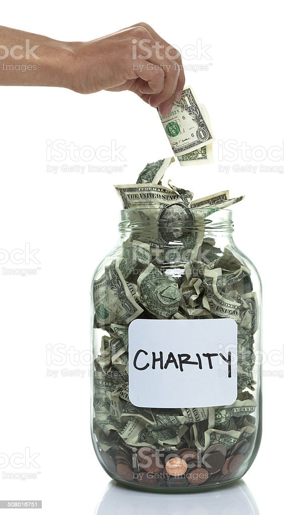 Hand putting money into jar with a white charity label stock photo